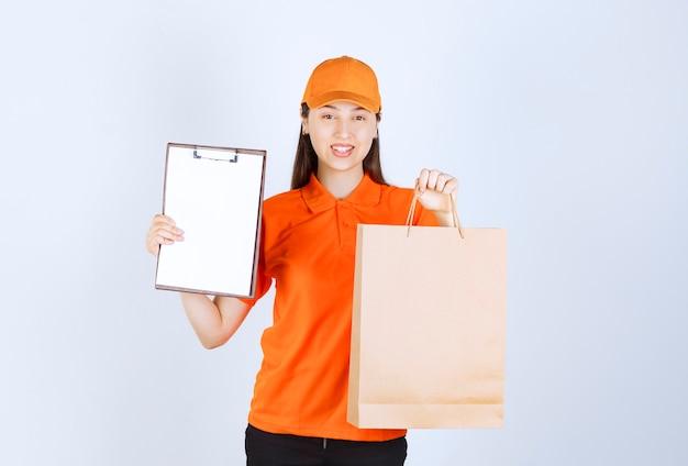 Weibliche servicemitarbeiterin in orangefarbener uniform, die eine einkaufstasche aus pappe hält und dem kunden die unterschriftenliste präsentiert.