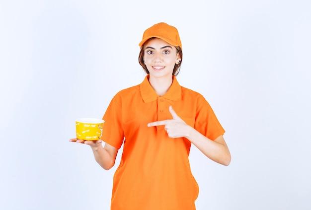 Weibliche servicemitarbeiterin in orangefarbener uniform, die eine gelbe tasse zum mitnehmen hält