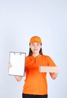 Weibliche servicemitarbeiterin in orangefarbener uniform, die einen karton hält und eine checkliste zur unterschrift vorlegt.