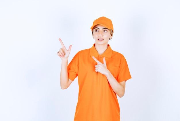 Weibliche servicemitarbeiterin in orangefarbener uniform, die mit emotionen auf etwas oben zeigt