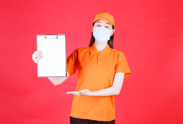 Weibliche servicemitarbeiterin in orangefarbener uniform und maske, die das projektblatt demonstriert und darauf zeigt.