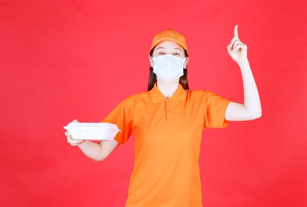 Weibliche servicemitarbeiterin in orangefarbener uniform und maske, die eine lebensmittelverpackung zum mitnehmen hält und nachdenklich und träumend aussieht.