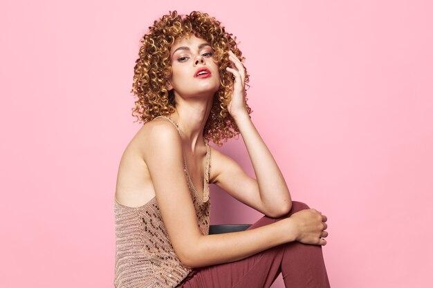 Weibliche sexy erscheinung lockige haare hosen stil porträt pailletten hemd wand