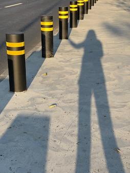 Weibliche silhouette, die schwarzen zaunpoller mit gelben reflektierenden streifen berührt