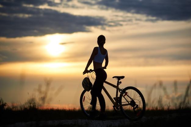 Weibliche silhouette mit fahrrad