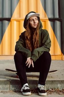Weibliche skaterin, die neben ihrem skateboarding draußen sitzt