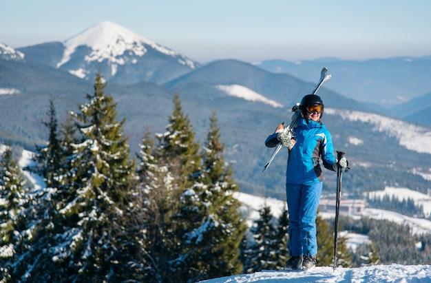 Weibliche skifahrerin, die auf einem berg mit skiern auf ihrer schulter atemberaubende landschaft steht