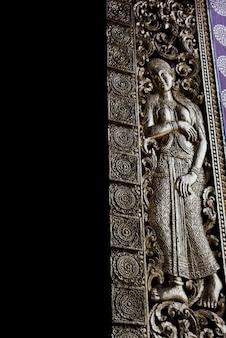 Weibliche skulptur schnitzte auf tür des tempels, wat xieng thong, luang prabang, laos