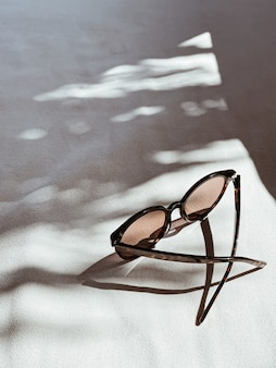 Weibliche sonnenbrille auf weißem hintergrund mit verschwommenen sonnenlichtschatten