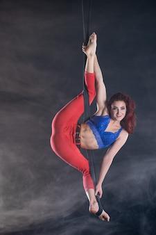 Weibliche sportliche, sexy und flexible luftzirkuskünstlerin mit rotschopf auf luftgurten.