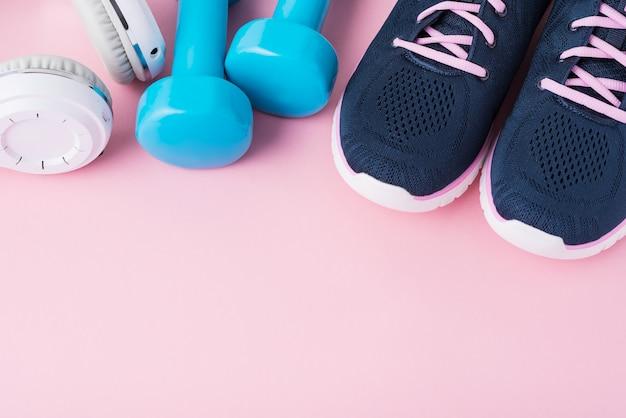 Weibliche sportschuhe, blaue dummköpfe und weiße kopfhörer mit kopienraum, draufsicht