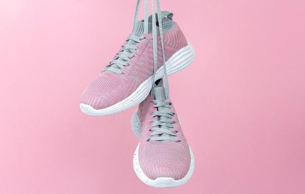 Weibliche sportschuhe für lauf oder fitness, die auf rosa hintergrund hängen