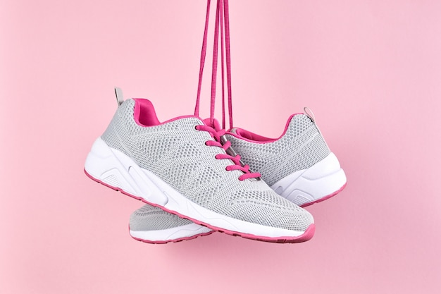 Weibliche sportschuhe für lauf und fitness auf rosa hintergrund. mode stilvolle sportschuhe, nahaufnahme