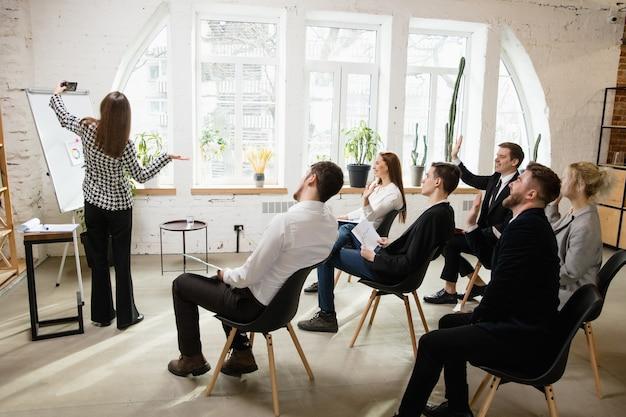 Weibliche sprecherin, die eine präsentation in der halle im workshop-publikum oder im konferenzsaal hält