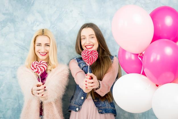 Weibliche stilvolle freunde, die spaß mit süßigkeiten und ballons auf dem blauen wandhintergrund haben
