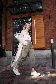 Weibliche stilvolle modell zu fuß stadt street fashion frau trägt trenchcoat übergroße cargohosen