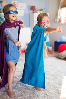 Weibliche superhelden, die von den kleinen mädchen vorgetäuscht wurden