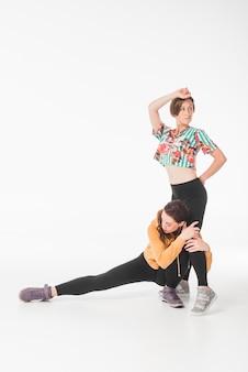 Weibliche tänzer, die gegen weißen hintergrund tanzen