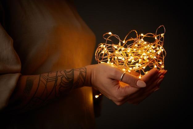 Weibliche tätowierungshände, die gelbe weihnachtslichtdekorationen halten