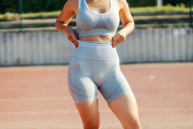 Weibliche taille in sportbekleidung. nahaufnahme eines torsos von einer frau in guter körperlicher verfassung, gekleidet in einem grauen sport-bh und shorts. bauchmuskeln und heißer körper im freien feld zum training