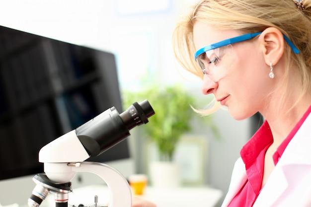 Weibliche tausendjährige chemiker in schutzbrillen