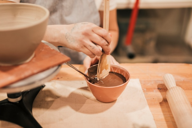 Weibliche töpferhand, welche die farbe für keramische schüssel in der werkstatt vorbereitet