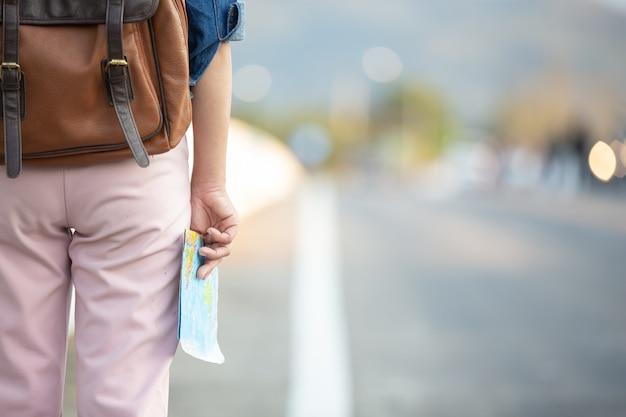 Weibliche touristen an hand haben eine glückliche reisekarte.