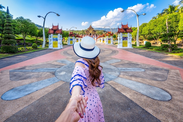 Weibliche touristen, die die hand des mannes halten und ihn zu ho kham luang nordthailändischem stil in royal flora ratchaphruek in chiang mai, thailand führen.