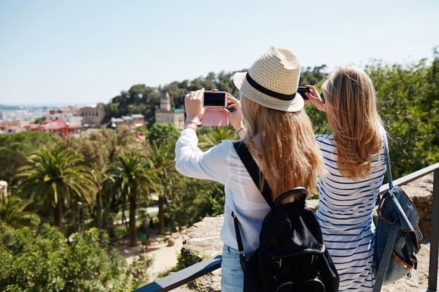 Weibliche touristen, die fotos im park machen