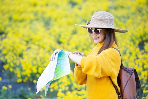 Weibliche touristen halten eine karte, um orte zu finden. Kostenlose Fotos