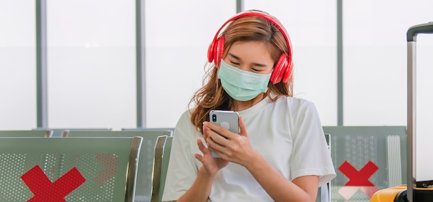 Weibliche touristen hören musik und tragen masken, um viren zu verhindern, während sie darauf warten, das flugzeug zu besteigen