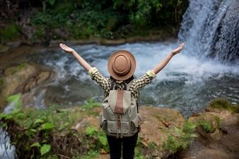 Weibliche Touristen sind glücklich und erfrischt am Wasserfall.