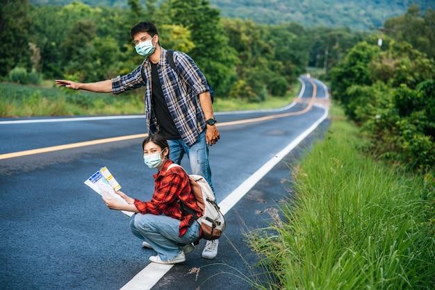 Weibliche touristen sitzen und schauen auf die karte, männliche touristen geben vor, per anhalter zu fahren. beide tragen masken und stehen am straßenrand.