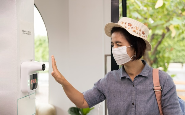 Weibliche touristen verwenden wand-infrarot-thermometer, bevor sie das restaurant betreten