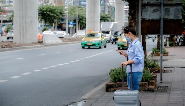 Weibliche touristen warten in der stadt auf ein taxi, indem sie mit der anwendung im smartphone ein auto anrufen.