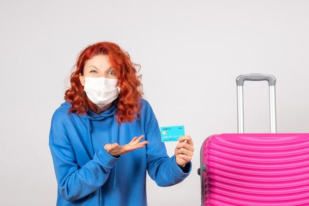 Weibliche touristin der vorderansicht, die bankkarte in maske hält