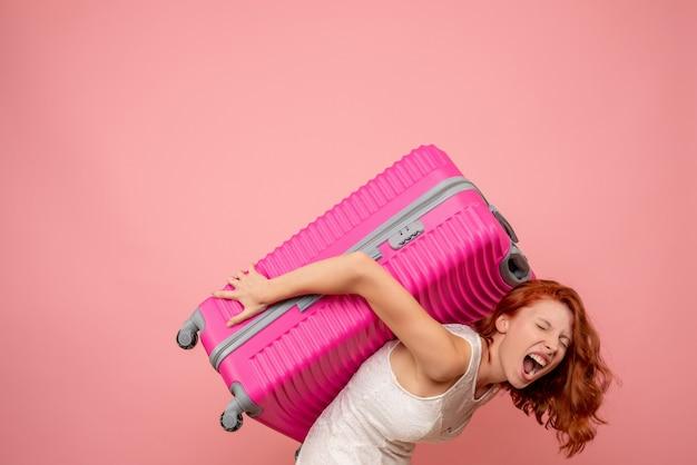 Weibliche touristin der vorderansicht, die ihre schwere rosa tasche trägt