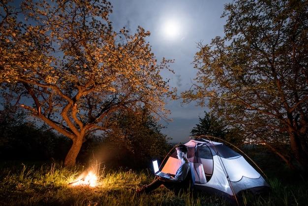 Weibliche touristin mit ihrem laptop auf dem campingplatz in der nacht. frau, die nahe lagerfeuer und zelt unter bäumen und nachthimmel mit dem mond sitzt