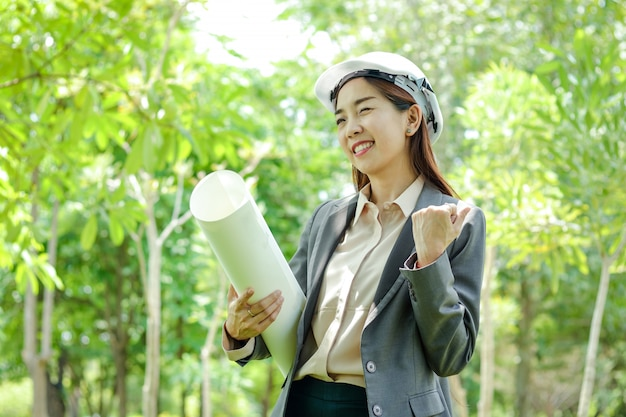 Weibliche umweltingenieure tragen einen papierhut, um die machbarkeit der konstruktion zu untersuchen.