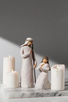 Weibliche und männliche figur des dreikönigstags mit neugeborenen und kerzen
