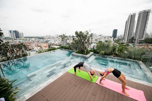 Weibliche und männliche freunde, die zusammen yoga im freien praktizieren