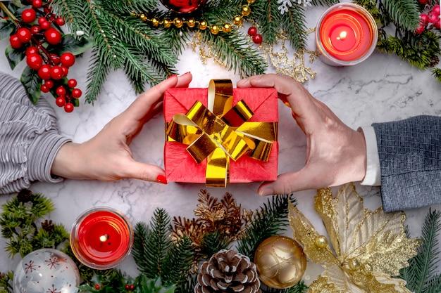 Weibliche und männliche hände, die rote weihnachtsgeschenkbox mit einem goldenen bogen auf weißem marmor geben. flache ansicht von oben. neujahrsfichtenzweige, zapfen, kugeln, luxuriöse golddekorationen. urlaubsstimmung