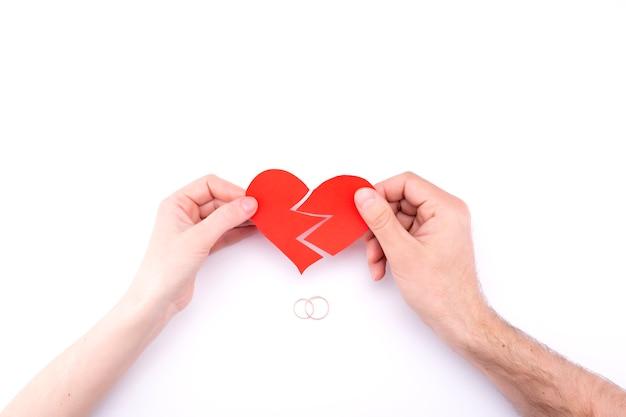 Weibliche und männliche hände halten ein gebrochenes herz auf einem weißen