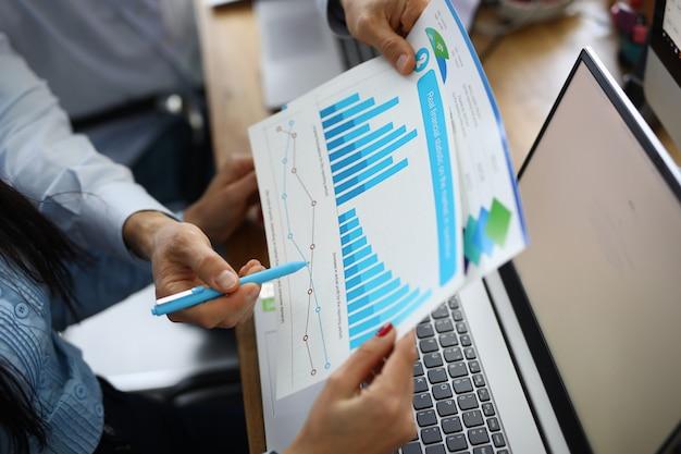 Weibliche und männliche hand, die grafik mit finanzieller leistung am arbeitsplatz hält.