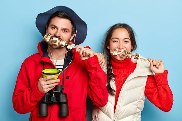 Weibliche und männliche touristen essen leckeren marshmallow, der am lagerfeuer geröstet wird, verbringen zeitvertreib in der natur, wie reisen und abenteuer, tragen freizeitkleidung