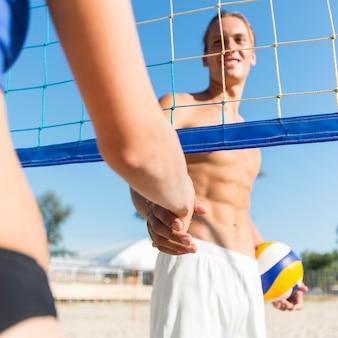 Weibliche und männliche volleyballspieler schütteln ihre hand unter dem netz