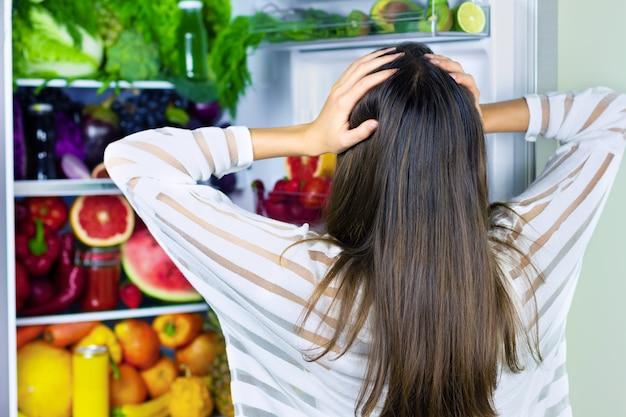Weibliche vegane vegetarische frau, die für kopfschock des gesunden bunten gemüses des antioxidans, des rohen saftes und der früchte für das essen nach dem markt im kühlschrank nimmt: grapefruit, tomaten, wassermelone, ananas