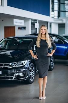 Weibliche verkäuferin in einem autosalon mit dem auto