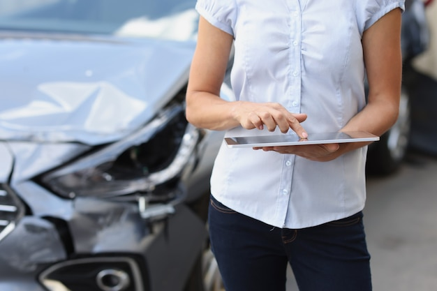 Weibliche versicherungsvertreterin gibt daten in das autoschadenprogramm ein, kaputtes autoversicherungskonzept