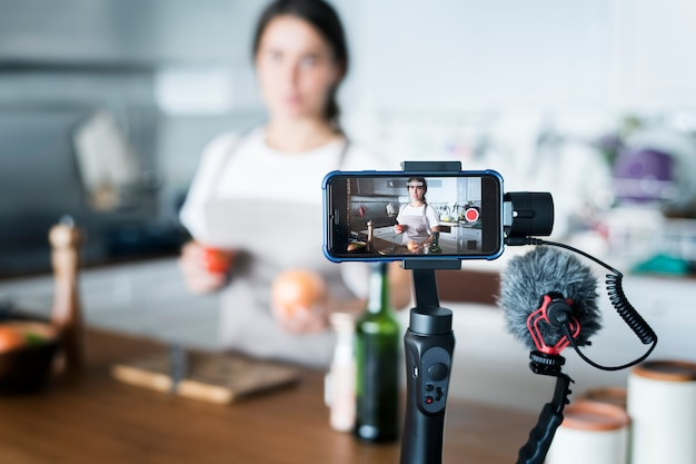 Weibliche vlogger-aufnahme, die zu hause in verbindung stehende sendung kocht